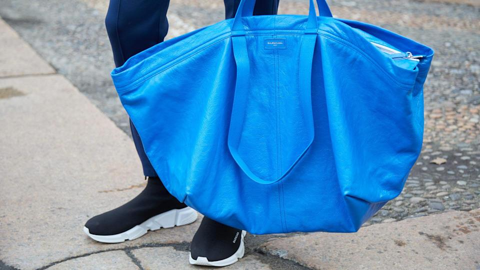 MILAN - FEBRUARY 24: Man with blue Balenciaga leather bag and black shoes before Tod's fashion show, Milan Fashion Week street style on February 24, 2017 in Milan.
