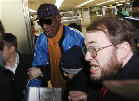 Bodyguards clear a path for Dennis Rodman as journalists surround him upon his arrival from North Korea's Pyongyang at Beijing Capital International Airport