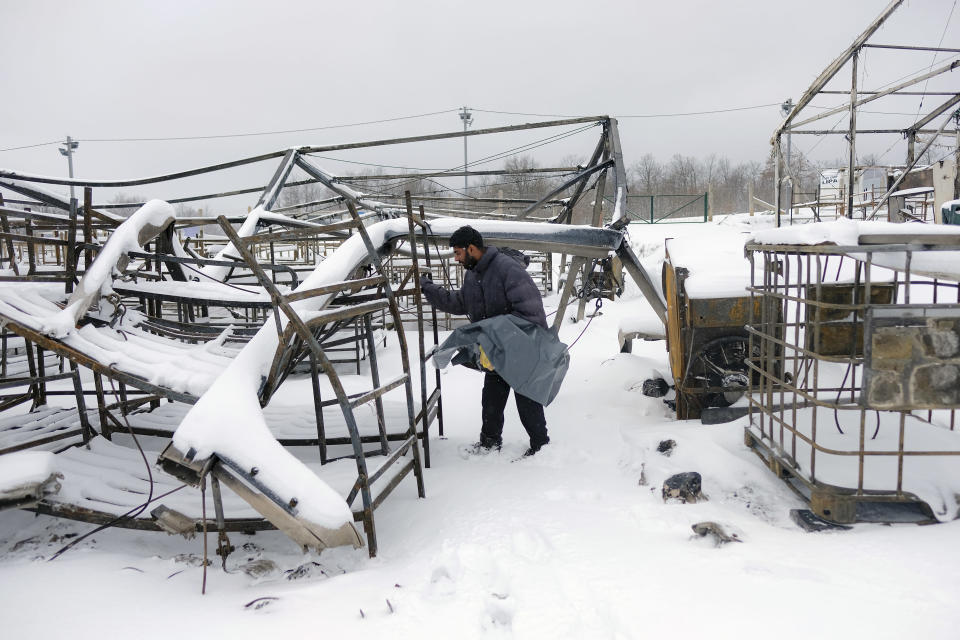 A migrant looks for belongings in the snow covered burnt out Lipa camp northwestern Bosnia, near the border with Croatia, Saturday, Dec. 26, 2020. Hundreds of migrants are stranded in a burnt-out squalid camp in Bosnia as heavy snow fell in the country and temperatures dropped during a winter spell of bad weather after fire earlier this week destroyed much of the camp near the town of Bihac that already was harshly criticized by international officials and aid groups as inadequate for housing refugees and migrants.(AP Photo/Kemal Softic)
