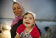 A Syrian refugee baby smiles in a tent at Suleymansah refugee camp in Akcakale in Sanliurfa province, Turkey, June 11, 2015. REUTERS/Osman Orsal
