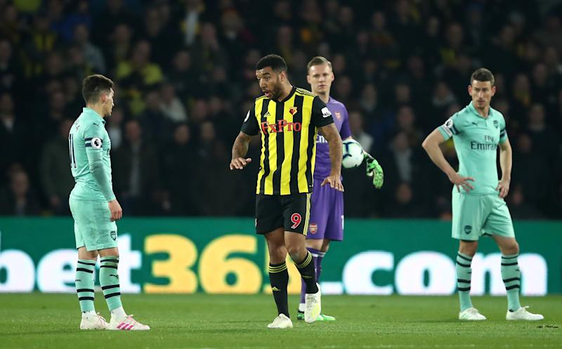 Troy Deeney of Watford leaves the field after being shown a red card for elbowing Lucas Torreira.