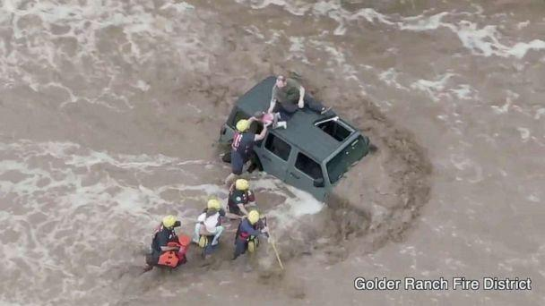 PHOTO: Firefighters rescue a man and two young girls who were stranded after their vehicle was washed away in flash floods near Tucson, Ariz., July 14, 2021. (Golder Ranch Fire District via Reuters)