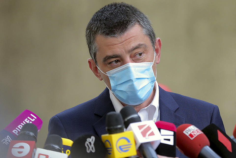 In this handout photo released by Georgia's Prime Minister Press Office, Georgia's Prime Minister Giorgi Gakharia, wearing a face mask to help curb the spread of the coronavirus, speaks to the media after voting at a polling station during the parliamentary elections in Tbilisi, Georgia, Saturday, Oct. 31, 2020. The hotly contested election between the Georgian Dream party, created by billionaire Bidzina Ivanishvili who made his fortune in Russia and has held a strong majority in parliament for eight years, and an alliance around the country's ex-President Mikheil Saakashvili, who is in self-imposed exile in Ukraine. (Georgia's Prime Minister Press office via AP)