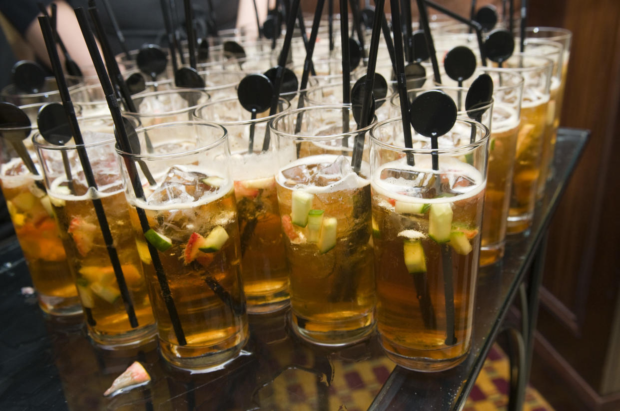 glasses full of pimms with fruit and straws stir sticks.  Narrow focus