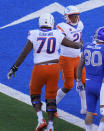 Boise State running back Andrew Van Buren, rear, is congratulated by offensive lineman John Ojukwu after a touchdown during the first half of the team's NCAA college football game against Air Force on Saturday Oct. 31, 2020, at Air Force Academy, Colo. (AP Photo/David Zalubowski)
