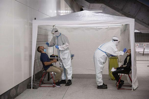 PHOTO: Members of the German Red Cross wear protective suits while taking throat swab samples at a COVID-19 testing station set up at the main railway station in Berlin, Germany, on Aug. 18, 2020. (Maja Hitij/Getty Images)