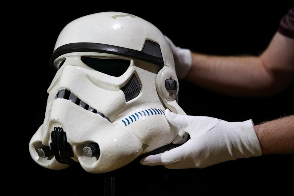 Embargoed to 0001 Tuesday August 20 A prop store employee adjusts a screen matched Tantive IV Stormtrooper helmet from 1977 film Star Wars: A New Hope (estimate ??120-180,000), during a preview of the forthcoming film and television memorabilia auction at the Prop Store head office near Rickmansworth.
