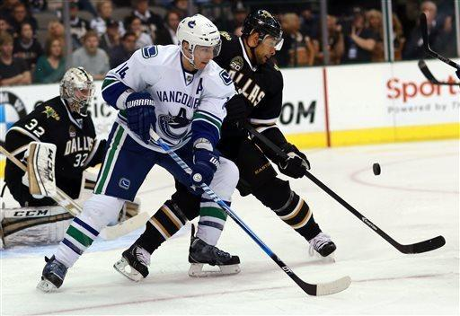Vancouver Canucks center Alex Burrows (14) looks for a shot on-goal as Dallas Stars defenseman Trevor Daley (6) defends during the second period of an NHL hockey game on Thursday, April 18, 2013 in Dallas. (AP Photo/ Michael Mulvey)