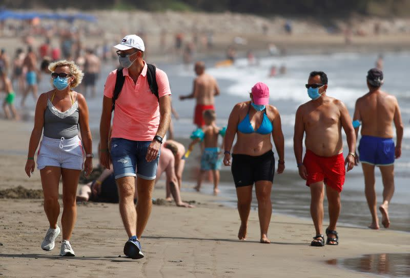 FILE PHOTO: Several people walk along the beach wearing face masks, as the regional government of the Canary Islands forbids smoking without maintaining a safe distance