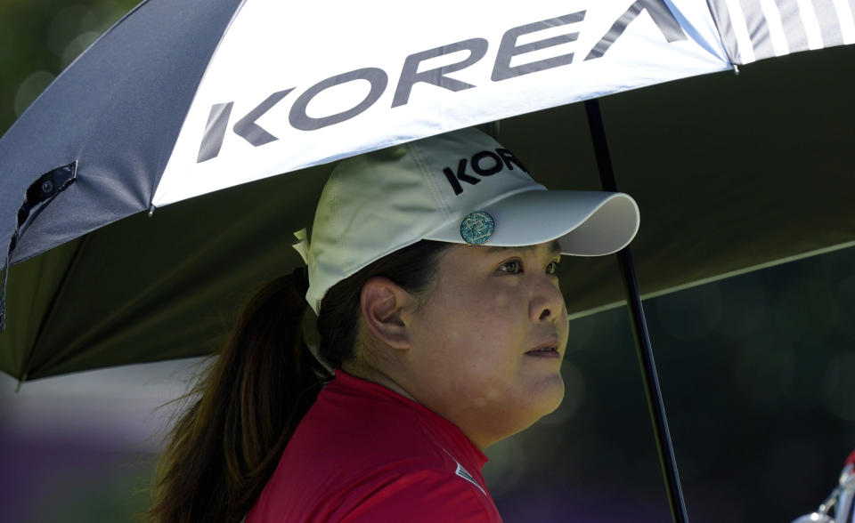 Inbee Park, of South Korea, stands under an umbrella on the 12th hole during the first round of the women's golf event at the 2020 Summer Olympics, Wednesday, Aug. 4, 2021, at the Kasumigaseki Country Club in Kawagoe, Japan. (AP Photo/Matt York)