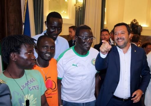 Italy's Interior Minister Matteo Salvini, right, speaks with farm labourers in Foggia, southern Italy, on Tuesday