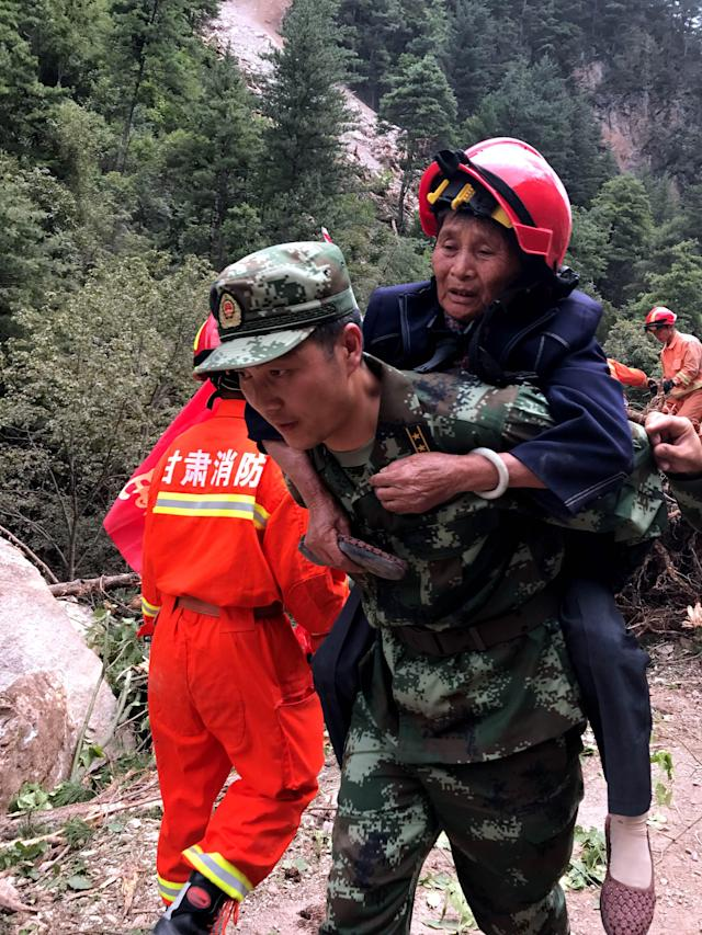 <p>A rescuer helps evacuate a woman following an earthquake in Jiuzhaigou in China's southwestern Sichuan province on Aug. 9, 2017. (Photo: STR/AFP/Getty Images) </p>