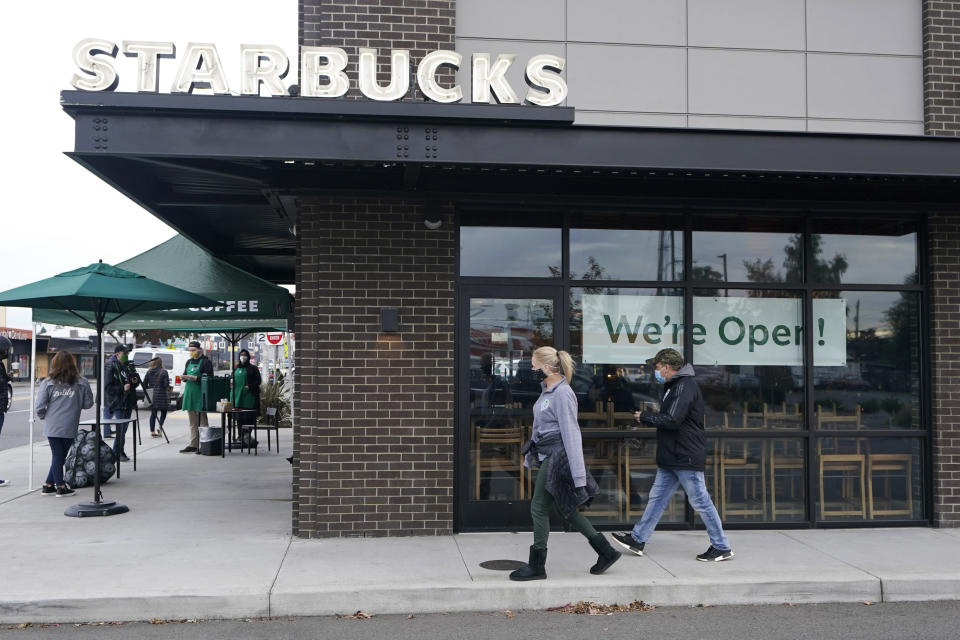"Customers walk past a sign that reads ""We're Open!"" at a Starbucks Coffee store in south Seattle, Tuesday, Oct. 27, 2020. Starbucks saw faster-than-expected recovery in the U.S. and China in its fiscal fourth quarter, giving it confidence as it heads into the holiday season. (AP Photo/Ted S. Warren)"