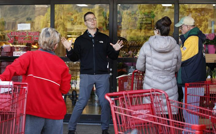 "An employee at the Trader Joe's store in Monrovia tells customers waiting in line that it would open doors to everyone at 9 a.m., not just seniors. <span class=""copyright"">(Al Seib/Los Angeles Times)</span>"