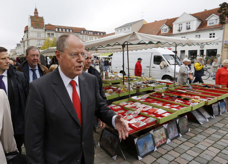FILE - In this Sept. 19, 2013 file picture Social Democratic top candidate Peer Steinbrueck walks over the market place during a stopover of his campaign trip in Neuruppin, about 40km northwest of Berlin, Germany. Steinbrueck is challenging Chancellor Angela Merkel in the general elections on Sunday, Sept. 22, 2013. (AP Photo/Ferdinand Ostrop.File)