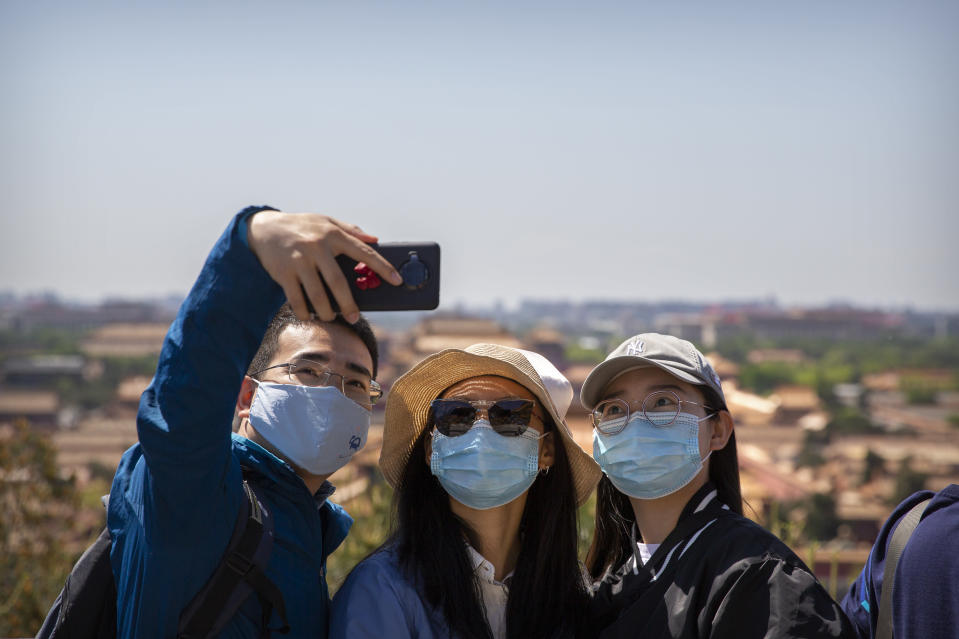 Visitors wearing face masks pose for a selfie at a viewing area overlooking the Forbidden City at a public park in Beijing, Saturday, May 1, 2021. Chinese tourists are expected to make a total of 18.3 million railway passenger trips on the first day of the country's five-day holiday for international labor day, according to an estimate by the state railway group, as tourists rush to travel domestically after the coronavirus has been brought under control in China.(AP Photo/Mark Schiefelbein)