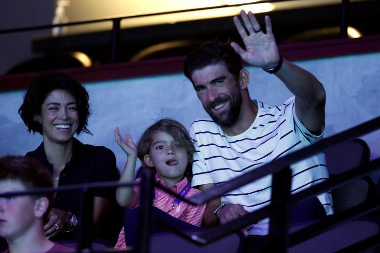 Retired Olympic swimming great Michael Phelps, his wife, Nicole, and son, Boomer, wave to fans at the US Olympic swimming trials in Omaha, Nebraska