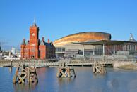 View of Cardiff city skyline from across the bay showing the Pier head building National Assembly for Wales and the millennium centre against a blue sky.