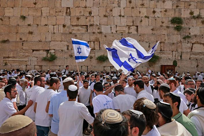"""Jewish men wave Israeli flags as they gather at the Western Wall, the holiest site where Jews are allowed to pray, near al-Aqsa mosque in the Old City of Jerusalem on May 10, 2021, as Israel marks """"Jerusalem Day."""""""