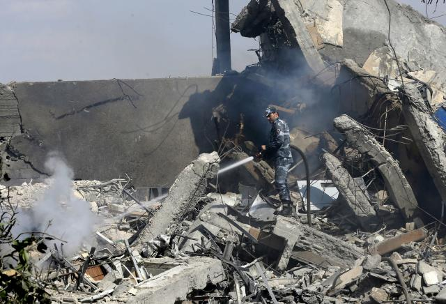 <p>A Syrian soldier sprays water on the wreckage of a building described as part of the Scientific Studies and Research Center (SSRC) compound in the Barzeh district, north of Damascus, during a press tour organised by the Syrian information ministry, on April 14, 2018. (Photo: Louai Beshara/AFP/Getty Images) </p>
