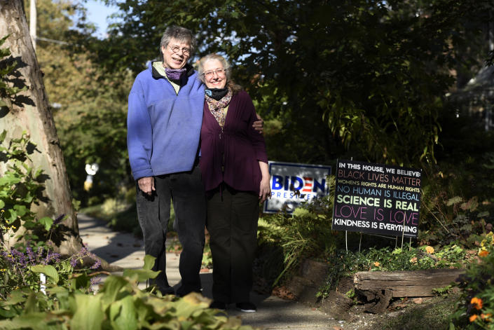 Ann Mintz, 73, and Clifford Wagner, 65, pose for a picture at their home, Tuesday, Oct. 6, 2020, in Philadelphia. The couple are debating whether to vote by mail or in person on Election Day. (AP Photo/Michael Perez)