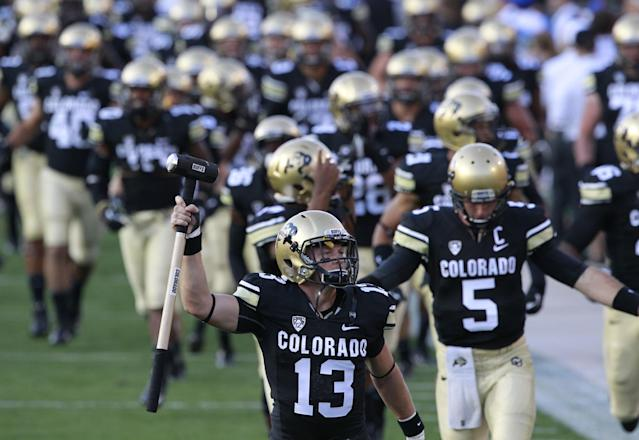 Colorado defensive back Parker Orms wields a sledgehammer as he leads his teammates on tot he field to face Central Arkansas in the first quarter of a college football game in Boulder, Colo., on Saturday, Sept. 7, 2013. (AP Photo/David Zalubowski)