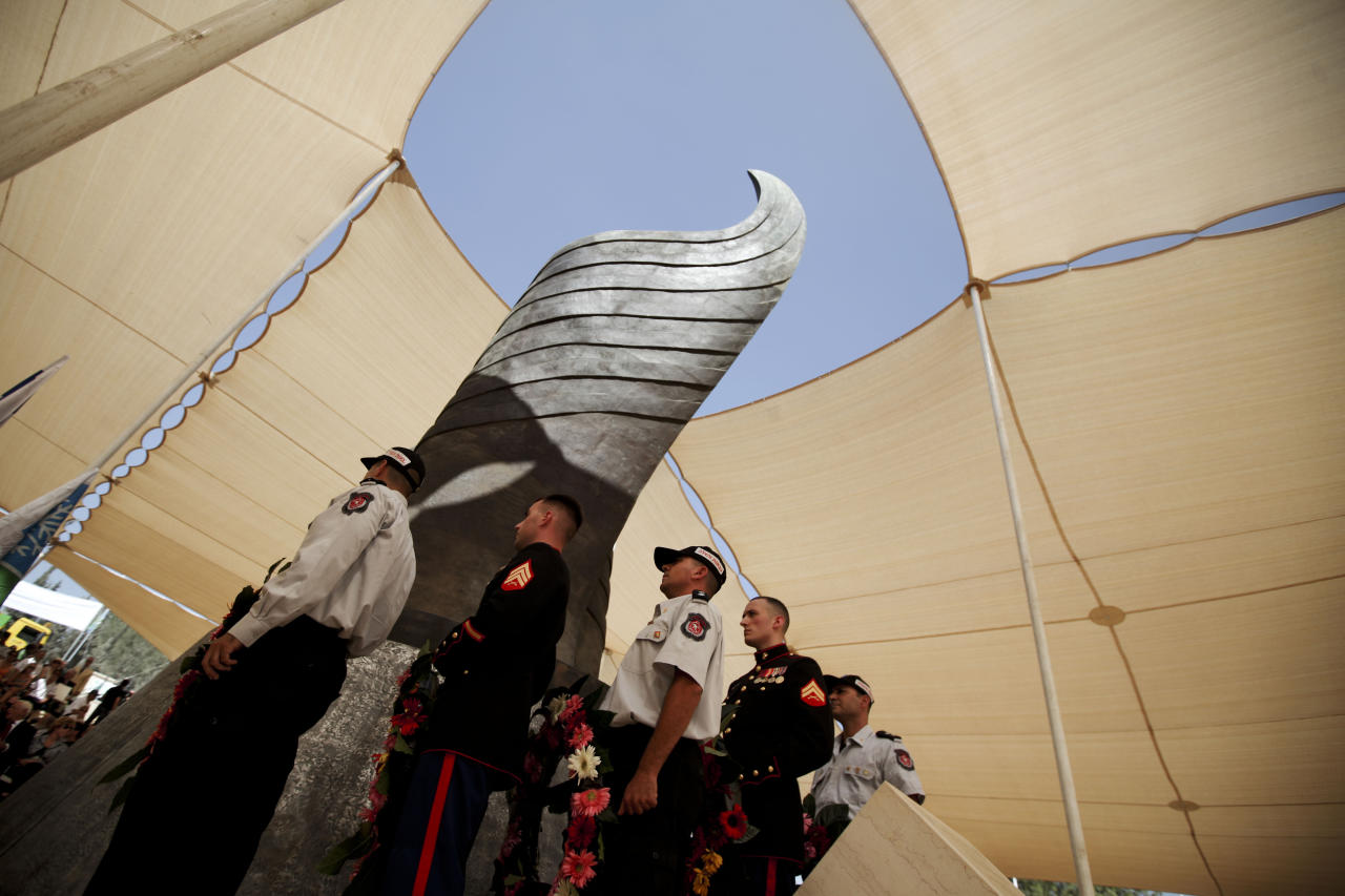 Israeli firefighters and U.S. naval officers hold wreaths as they prepare to lay them during a ceremony marking the 10th anniversary of the Sept. 11, 2001 terror attacks, at a memorial site for the victims just outside Jerusalem, Israel, Sunday, Sept. 11, 2011. (AP Photo/Tara Todras-Whitehill)