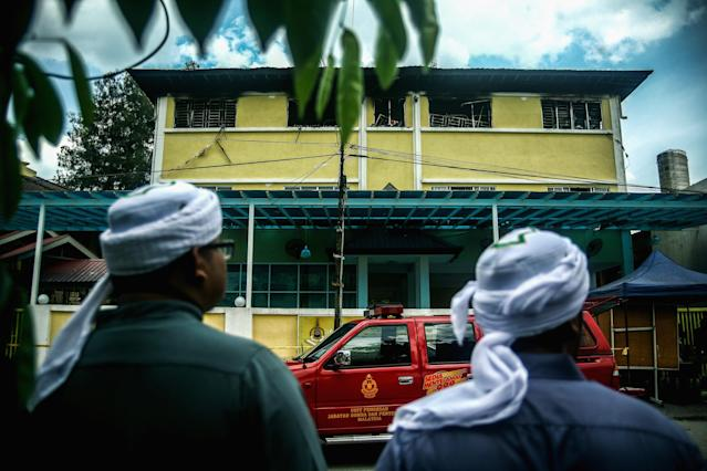 <p>Malaysian Muslims look at the view of religious school Darul Quran Ittifaqiyah after a fire broke out on Sept. 14, 2017 in Kuala Lumpur, Malaysia. (Photo: Mohd Samsul Mohd Said/Getty Images) </p>