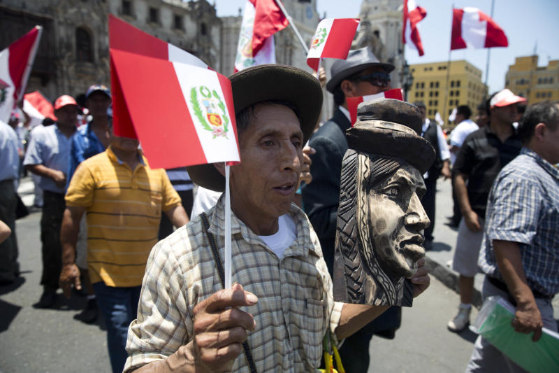 A man holding a Peruvian national flag and an Andean female face sculpture, attends a ceremony in front of government palace celebrating the World Court decision on the Peru-Chile maritime border, in Lima, Peru, Monday, Jan. 27, 2014. The United Nations' highest court set a maritime boundary between Chile and Peru on Monday, granting the latter a bigger piece of the Pacific Ocean but keeping rich coastal fishing grounds in Chilean hands. (AP Photo/Martin Mejia)