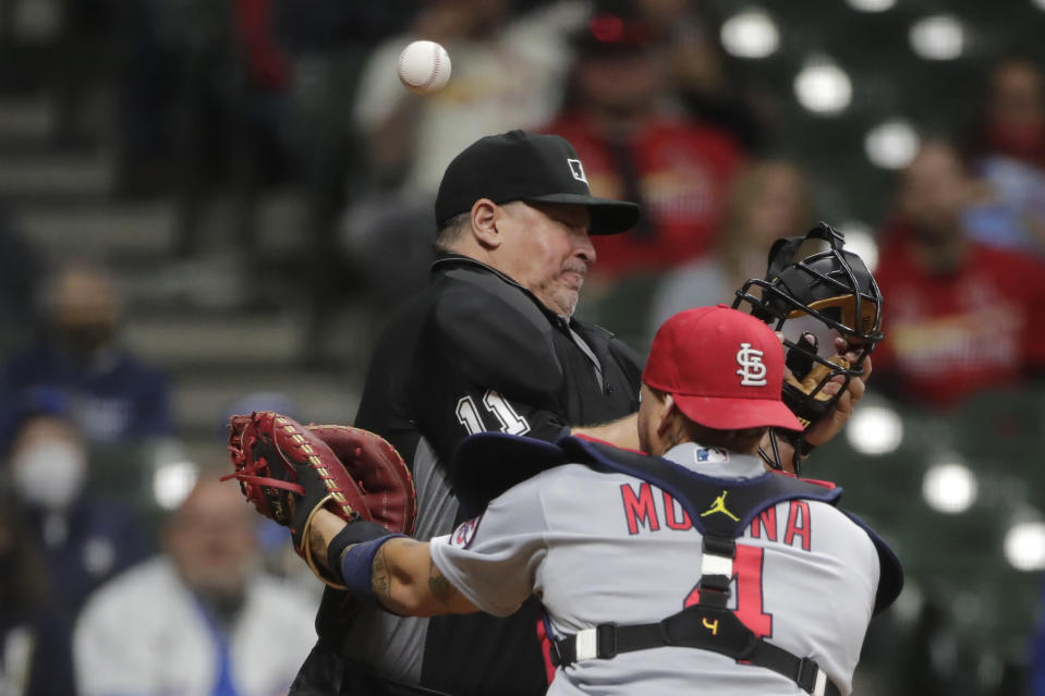 St. Louis Cardinals' Yadier Molina is unable to catch a bunt foul by Milwaukee Brewers' Freddy Peralta after colliding with umpire Tony Randazzo during the fifth inning of a baseball game Tuesday, May 11, 2021, in Milwaukee. (AP Photo/Aaron Gash)