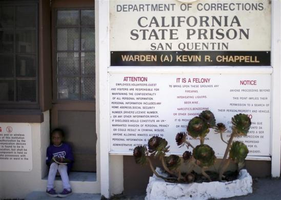 Sunshine, 7, sits outside San Quentin state prison after visiting her father Kinney, who said he was serving life for murder, in San Quentin, California June 8, 2012.