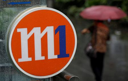 FILE PHOTO: A woman with an umbrella passes an M1 sign in Singapore