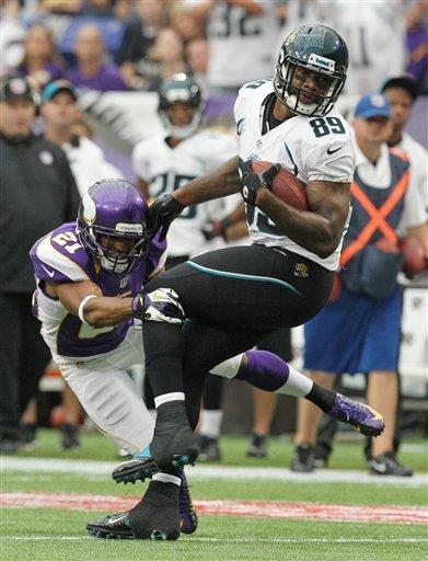 Jacksonville Jaguars tight end Marcedes Lewis (89) tries to break a tackle by Minnesota Vikings cornerback Josh Robinson, left, during the first half of an NFL football game on Sunday, Sept. 9, 2012, in Minneapolis. (AP Photo/Genevieve Ross)