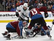 Colorado Avalanche goaltender Philipp Grubauer, front left, covers the puck after stopping a redirected shot off the stick of San Jose Sharks right wing Timo Meier, back, as Colorado center Alexander Kerfoot, front center, and left wing Gabriel Landeskog defend during the second period of Game 3 of an NHL hockey second-round playoff series Tuesday, April 30, 2019, in Denver. (AP Photo/David Zalubowski)