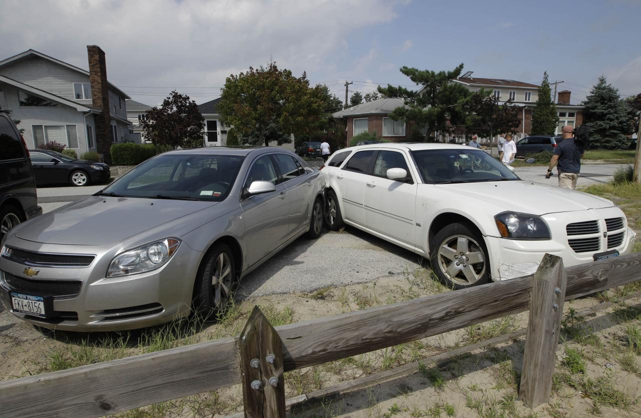 Two cars that collided into each other remain at a 45 degree angle after a possible tornado touched down in the Breezy Point neighborhood in New York, Saturday, Sept. 8, 2012. A tornado swept out of the sea and hit the beachfront neighborhood in New York City, hurling debris in the air, knocking out power and startling residents who once thought of twisters as a Midwestern phenomenon. Firefighters were still assessing the damage, but no serious injuries were reported and the area affected by the storm appeared small. (AP Photo/Kathy Willens)