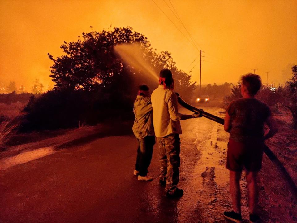 Residents hold a hose aimed at a wildfire on Evia island. Source: EPA