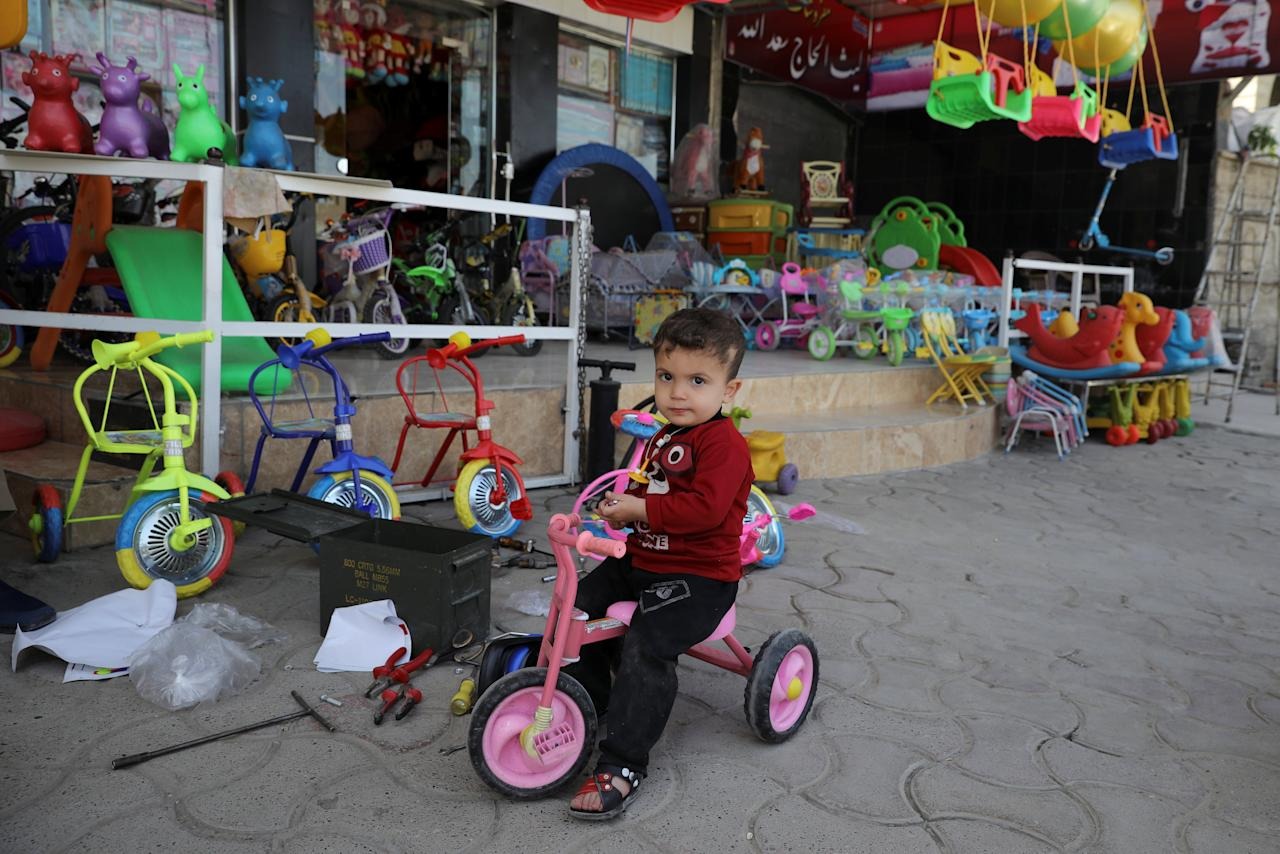 A boy sits on his bicycle in front of a toy store, in eastern Mosul, Iraq April 21, 2017. Picture taken April 21, 2017. REUTERS/Marko Djurica