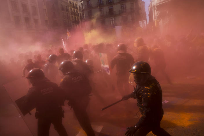 Catalan police officers clash with pro independence demonstrators on their way to meet demonstrations by member and supporters of National Police and Guardia Civil, as coloured powder is seen in the air after being thrown by protesters, in Barcelona on Saturday, Sept. 29, 2018. (AP Photo/Emilio Morenatti)