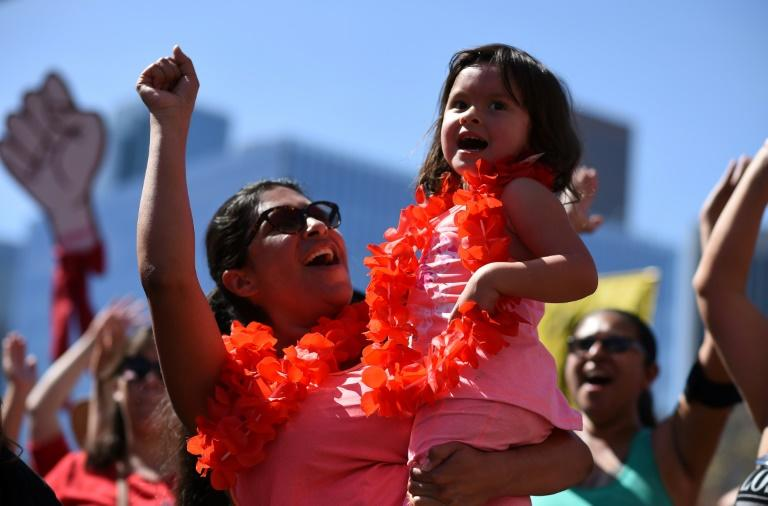 "A mother and daughter cheer at the ""A Day Without a Woman"" rally honoring International Women's Day, in Los Angeles, California"