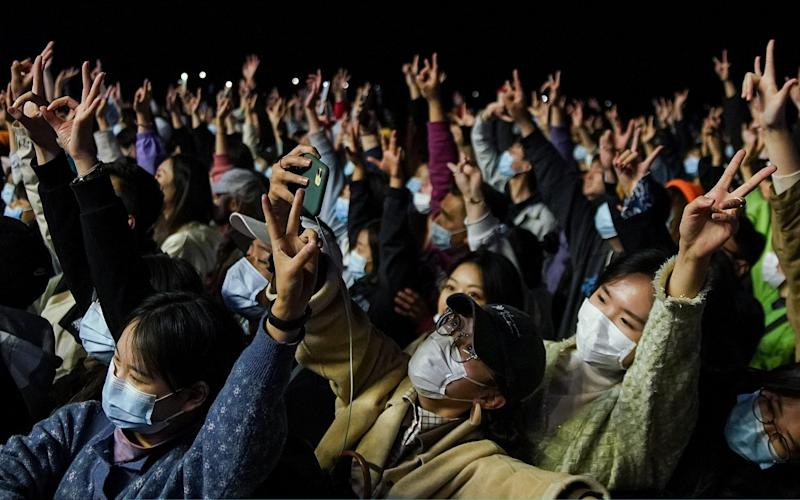 Chinese rock fans wear protective masks as they enjoy a performance at the RYE Music Festival - Getty