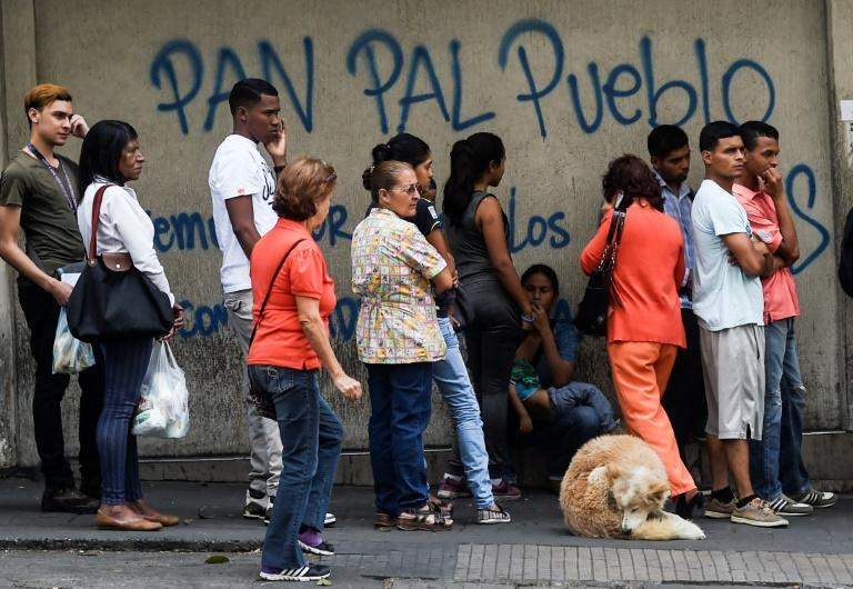 People queue outside a bakery in Caracas to buy bread which has become all but impossible to find at many Venezuelan bakeries