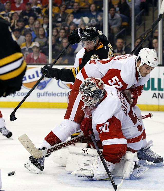 Detroit Red Wings goalie Jonas Gustavsson (50) and defenseman Jonathan Ericsson (52) protect the goal against Boston Bruins right wing Reilly Smith (18) who tries to get to the puck near the crease in the second period of an NHL hockey game in Boston, Monday, Oct. 14, 2013. (AP Photo/Elise Amendola)