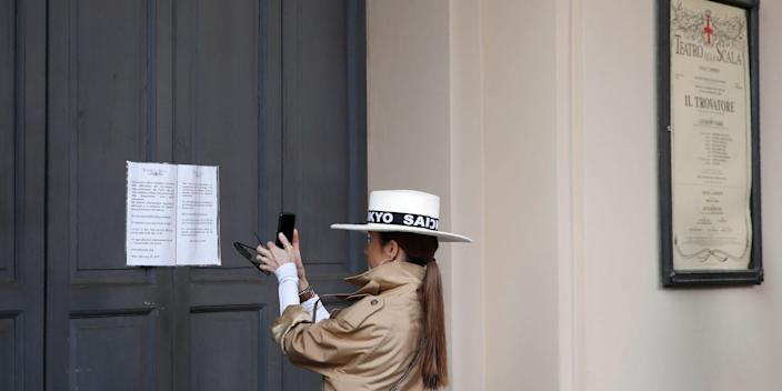 A woman takes a picture of a notice on the entrance doors, written in Italian and English, advising that La Scala theater performances are suspended due to the spread of coronavirus, in Milan, Italy, Sunday, Feb. 23, 2020.