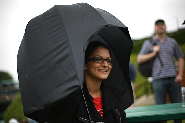 LONDON, ENGLAND - JUNE 27: A spectator waits for play to resume under a wrap around umbrella on day four of the Wimbledon Lawn Tennis Championships at the All England Lawn Tennis and Croquet Club on June 27, 2013 in London, England. Play has been disrupted on some courts due to rain. (Photo by Peter Macdiarmid/Getty Images)