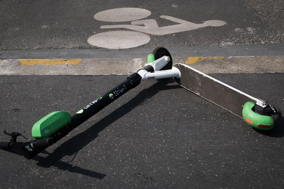 An electric scooter of US company Lime lies on the pavement