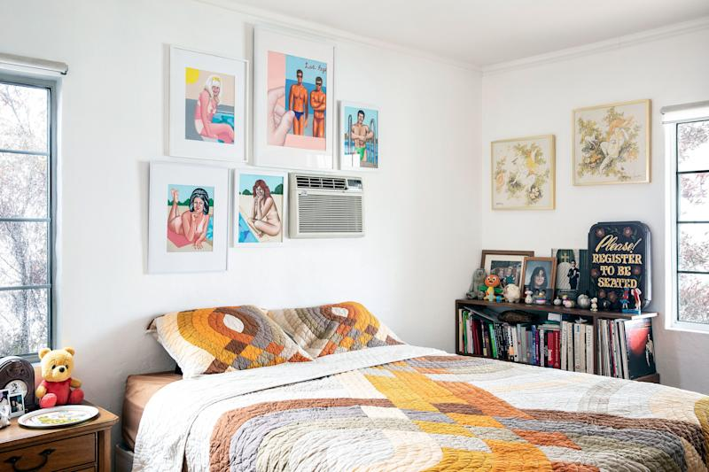 In the bedroom, a cluster of paintings by Juliette Toma draw attention away from the wall A/C unit.