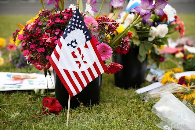 """<p>A flag bearing an abbreviation for """"Portland"""" stands at a makeshift memorial for two men who were killed on a commuter train while trying to stop another man from harassing two young women who appeared to be Muslim, in Portland, Ore., May 29, 2017. (Terray Sylvester/Reuters) </p>"""
