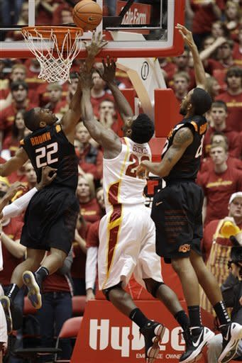 Iowa State forward Anthony Booker, center, fights for a rebound with Oklahoma State guard Markel Brown, left, and forward Michael Cobbins, right, during the first half of an NCAA college basketball game, Wednesday, Jan. 18, 2012, in Ames, Iowa. (AP Photo/Charlie Neibergall)