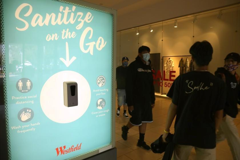 "ARCADIA, CA - OCTOBER 07, 2020 - Shoppers walk past a ""Sanitize on the Go,"" station to keep shoppers safe from coronavirus at the Westfield Santa Anita shopping mall in Arcadia on October 7, 2020. This is the first day customers return to indoor shopping after Los Angeles County eases restrictions and have reopened the malls and the individual stores. Such stores have been closed for weeks, but reopened Wednesday at 25% capacity. Westfield Santa Anita has placed Covid-related signage with one-way traffic, 6 feet distancing when waiting to get into individual stores, hand sanitizing stations and mask are required before entering the mall. (Genaro Molina / Los Angeles Times)"
