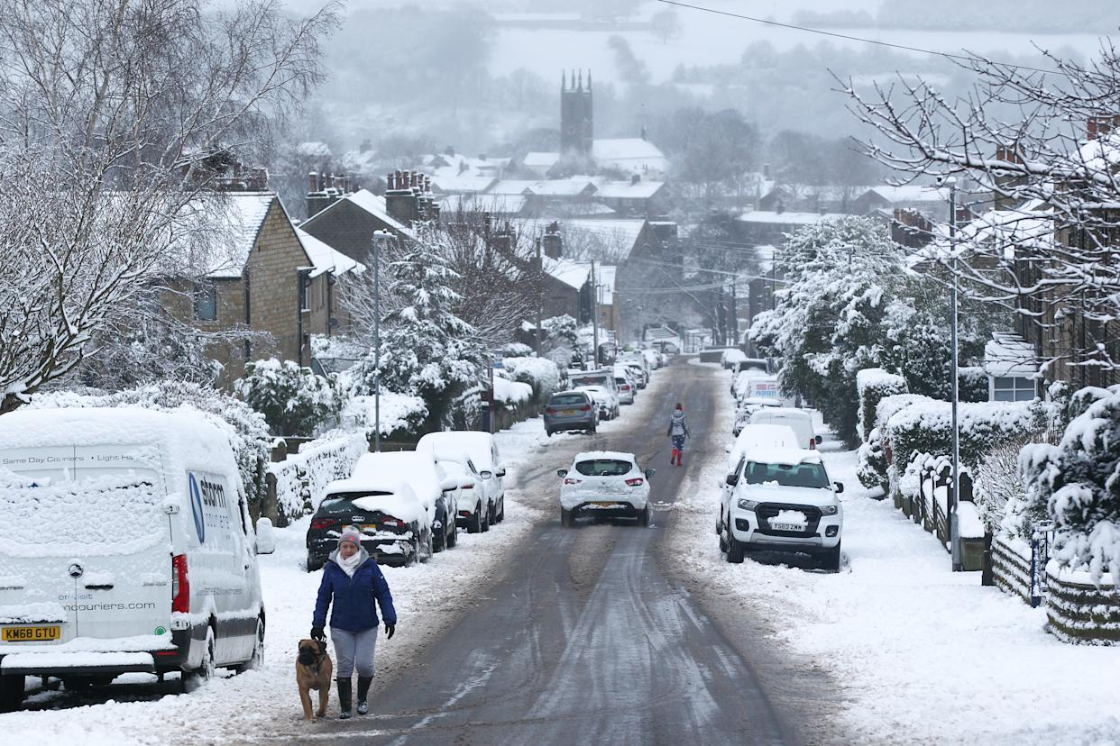 A person walks his dog on a snowy morning in the West Yorkshire village of Honley. Heavy snow fell overnight in West Yorkshire, causing dangerous driving conditions. (Photo by Adam Vaughan / SOPA Images/Sipa USA)